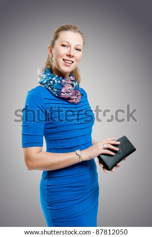 A girl with a purse on a gray background - stock photo