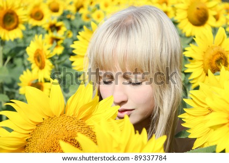 A girl with closed eyes among sunflowers getting pleasure from nature - stock photo