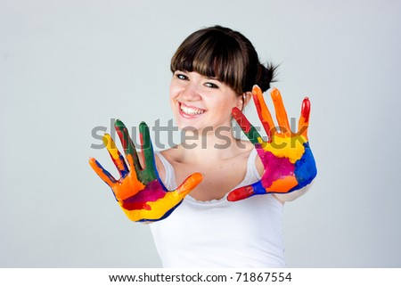 A girl with colored hands on a gray background - stock photo