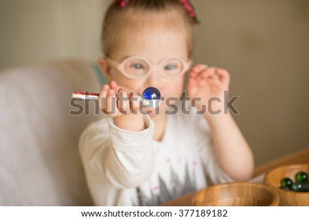 a girl with Down syndrome are trained at Montessori - stock photo