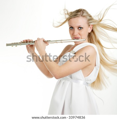 A girl with freckles playing on flute - stock photo