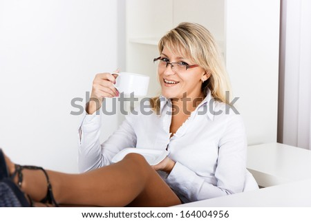 A girl with glasses resting with a cup of coffee in the office - stock photo