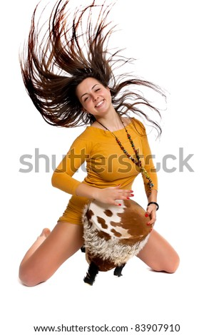 A girl with long hair, ethnic drum beats in the studio posing on a white background