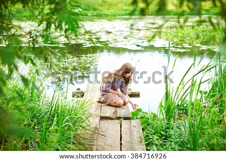 A girl with long hair sitting on the beach. The teenager looks at the water. The child  on the bridge by the river. Lots of lush greenery.