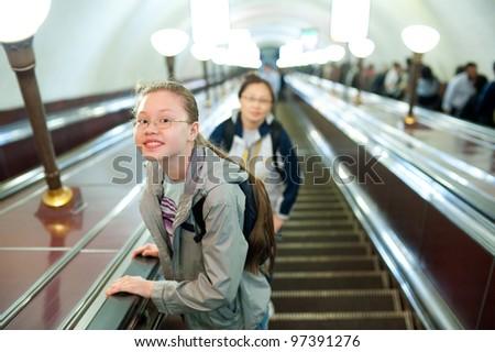 a girl (11 years) lifts on a metro escalator - stock photo