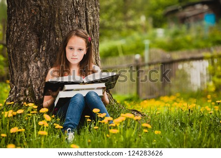 A girl 11 years old reads a book in the meadow.
