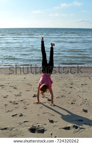 A girls with the hand state on the sandy beach on the North Sea coast