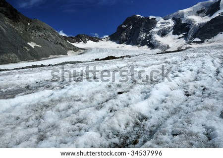 a glacier in the mountains. In the foreground, water melted by the sunforms little streams on the surface. Global warming is causing the glaciers to shrink - stock photo