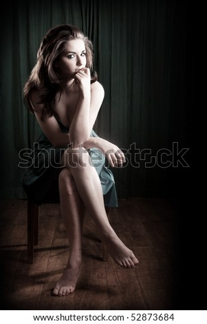 A glamorous young woman sitting on a stool and looking to the camera. - stock photo