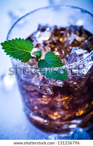 a glas with a rum, ice and lime cocktail - stock photo