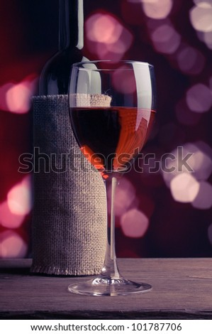 A glass and a bottle of red wine. - stock photo