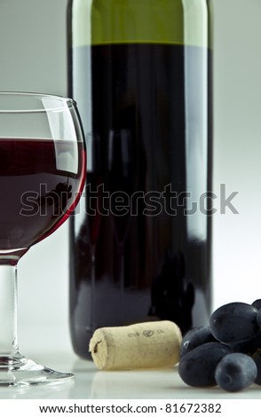 A glass and a bottle of red wine - stock photo