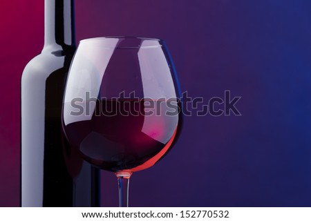 a glass and bottle of rose wine against colored background blue and magenta - stock photo