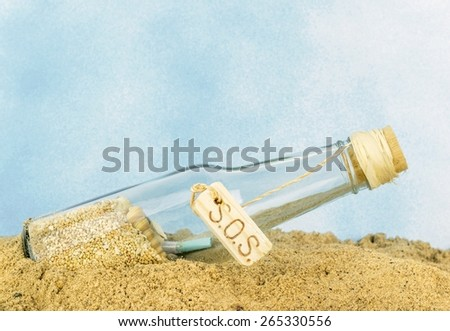 A glass bottle with SOS in sand on a blue background with copy space for your text - stock photo