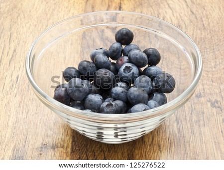 a glass cup of blueberries on wooden table - stock photo