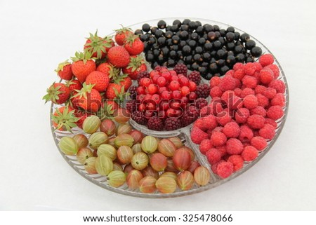 A Glass Dish Displaying a Variety of Fresh Fruit Berries. - stock photo