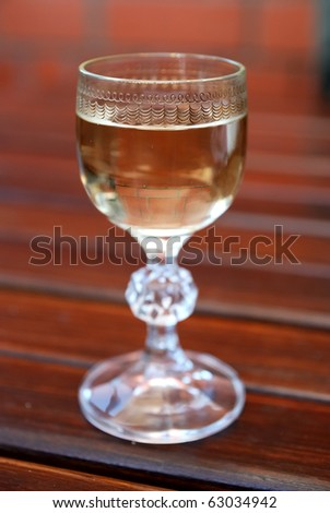 a glass filled with whiskey on wood background. Shallow depth of field - stock photo