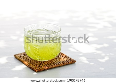 A glass full of a lime colored drink on a woven coaster. - stock photo