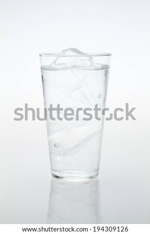 A glass full of ice cubes and water. - stock photo