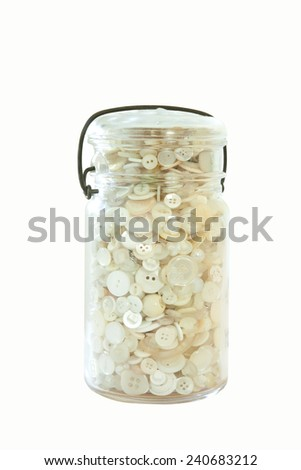 A glass jar of white buttons isolated on white - stock photo