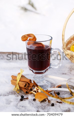A glass mug filled with hot mulled red wine, orange peels and spices (Gluhwein) on a snowy table, vertical - stock photo