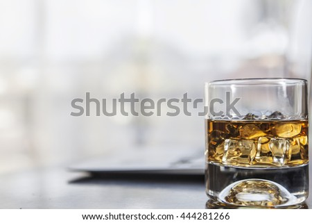 A glass of alcohol near laptop on table - stock photo