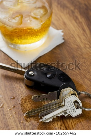 A glass of alcohol on top of a bar table along with a set of car keys. - stock photo