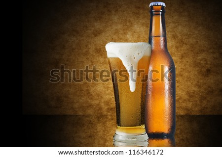A glass of beer and beer bottle on yellow background - stock photo