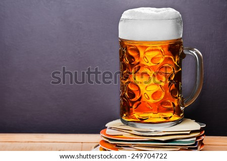 a glass of beer coasters on the background of slate wall