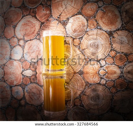 A glass of beer on a wooden background - stock photo