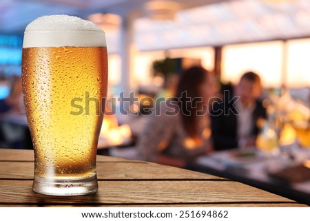 A glass of beer on the bar counter. Closeup.