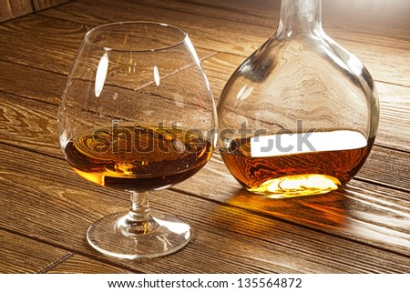 a glass of brandy and a bottle on a brown table