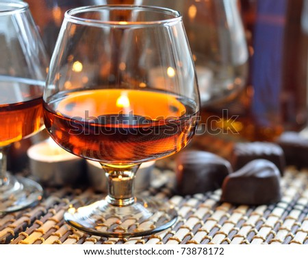 a glass of brandy, sweet and a candle - stock photo