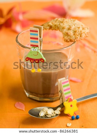 A glass of cacao with cookie and toy for kids. Selective focus - stock photo
