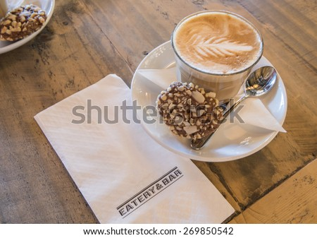 A glass of cappuccino with art foam of fern leaf design.  The hot drink is served with nuts cookie on a white saucer placed on wooden table.  Beside is a white paper napkin that can have text. - stock photo