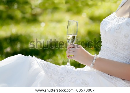 A glass of champagne in the hand of bride in landscape orientation, focused to glass - stock photo