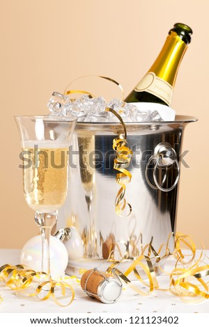 A glass of Champagne with a bottle in an ice bucket and gold streamers across the table - stock photo