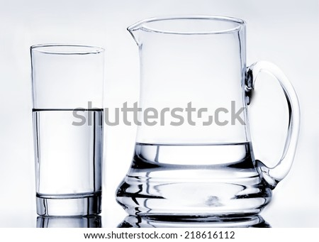 A glass of clean, clear, pure water standing beside a pitcher that is half full of water.  The items are shot from straight in front using the bright field lighting technique to capture the edges. - stock photo