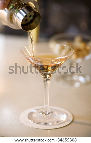 A glass of cocktail pouring from the shaker at a bar - stock photo