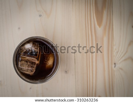 A glass of cola with ice on old wood textured - stock photo