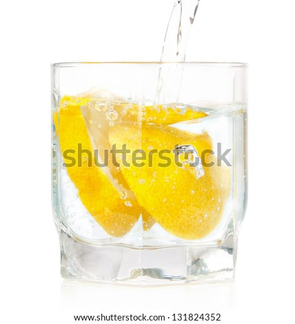 A glass of cold drink with a lemon from the fridge. On a white background. - stock photo