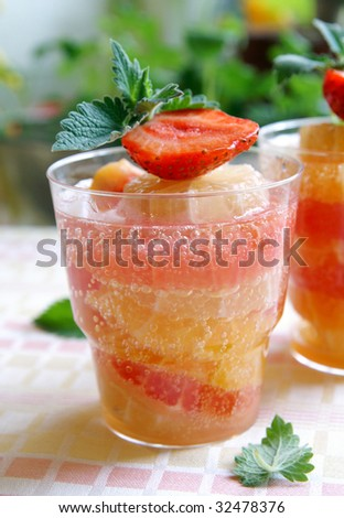 A glass of cooling citrus (lemon, orange, grapefruit) drink decorated with fresh strawberry and mint leaves, green blur background, closeup - stock photo