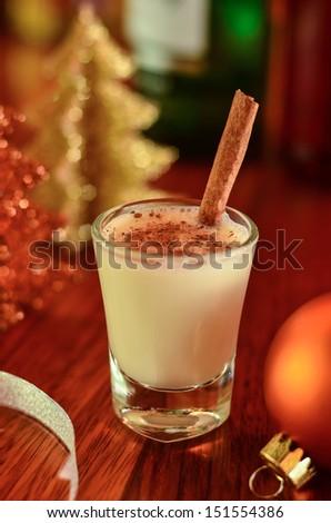 A glass of eggnog with Christmas stuff  - stock photo