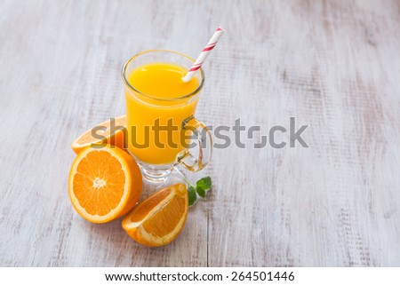 A glass of fresh breakfast orange juice drink with slices of orange and a straw - stock photo