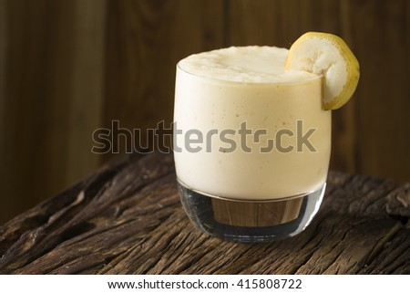 A Glass of fresh mango or banana fruit smoothie, on a rustic wooden background.