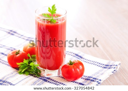 A glass of fresh tomato juice on the table - stock photo