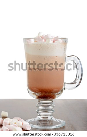 A glass of hot chocolate with marshmallows against on the table - stock photo