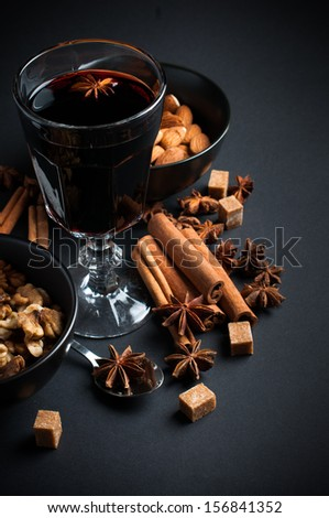 A glass of hot mulled wine, spices, cinnamon, star anise, brown sugar and nuts on a black background in studio - stock photo