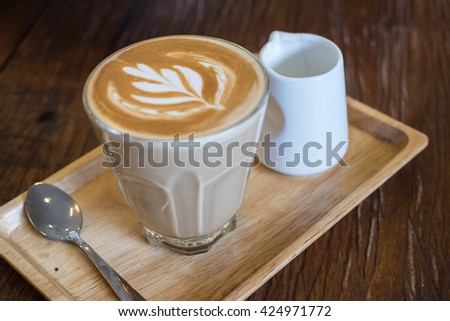 A glass of hot Piccolo latte coffee in wood tray on wooden table in coffee shop. - stock photo
