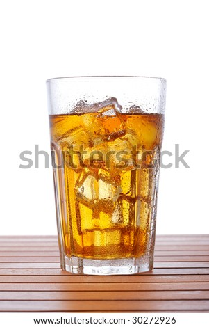 A glass of ice tea on wooden background. Shallow depth of field - stock photo